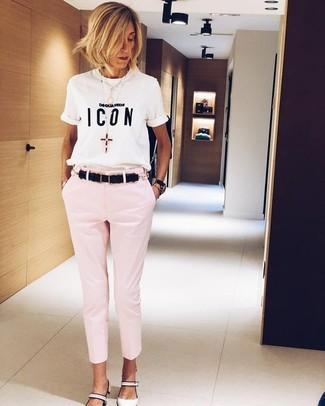 Cómo combinar: correa de cuero negra, zapatos de tacón de cuero blancos, pantalones pitillo rosados, camiseta con cuello circular estampada en blanco y negro