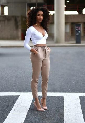 Cómo combinar: collar dorado, zapatos de tacón de cuero rosados, pantalón de pinzas marrón claro, jersey corto blanco