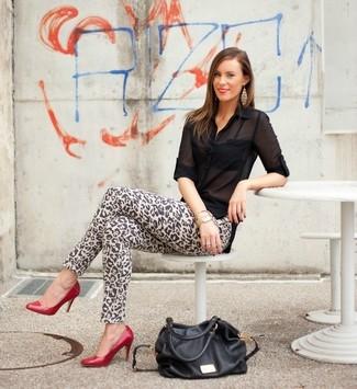 Cómo combinar: bolsa tote de cuero negra, zapatos de tacón de cuero rojos, vaqueros pitillo de leopardo marrón claro, blusa de botones de gasa negra