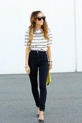 Cómo combinar: cartera sobre de cuero amarilla, zapatos de tacón de cuero negros, vaqueros pitillo negros, blusa de manga corta estampada gris