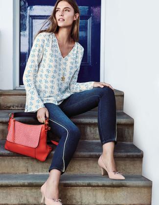 Cómo combinar: bolso de hombre de cuero rojo, zapatos de tacón de cuero en beige, vaqueros pitillo azul marino, blusa de manga larga estampada en blanco y azul