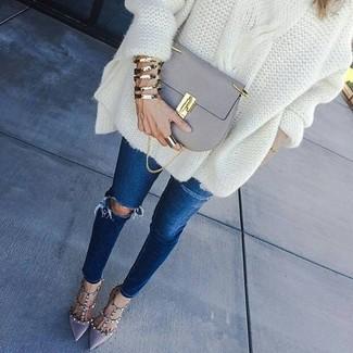 Cómo combinar: bolso bandolera de cuero gris, zapatos de tacón de cuero grises, vaqueros pitillo desgastados azul marino, jersey oversized de punto blanco