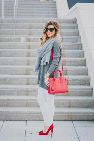 Cómo combinar: bolso bandolera de cuero rojo, zapatos de tacón de ante rojos, vaqueros pitillo blancos, túnica de punto gris