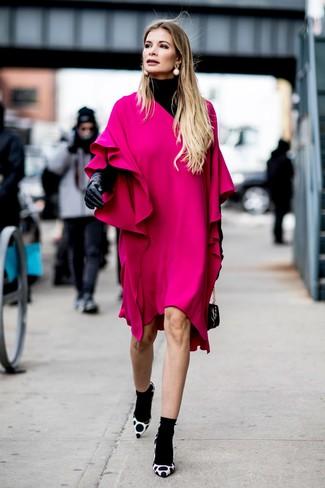Cómo combinar: cartera de cuero negra, zapatos de tacón de ante a lunares en blanco y negro, vestido recto con volante rosa, jersey de cuello alto negro