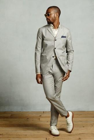 Cómo combinar: pañuelo de bolsillo estampado azul marino, zapatos derby de ante blancos, camisa de vestir de tartán en beige, traje gris