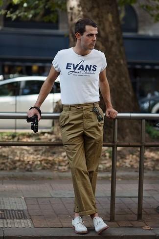 Look de moda: Gafas de sol verde oscuro, Zapatos derby de ante blancos, Pantalón chino verde oliva, Camiseta con cuello circular estampada en blanco y azul marino