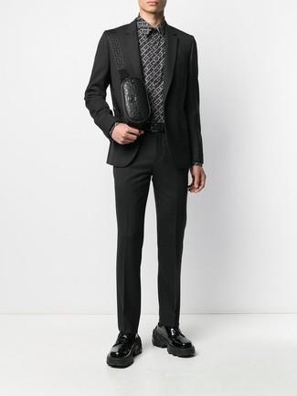 Cómo combinar: riñonera de cuero negra, zapatos derby de cuero gruesos negros, camisa de vestir estampada en negro y blanco, traje negro