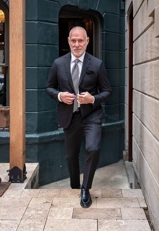 Outfits hombres: Elige un traje en gris oscuro y una camisa de vestir blanca para una apariencia clásica y elegante. Para darle un toque relax a tu outfit utiliza zapatos derby de cuero negros.