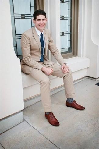 Outfits hombres: Considera emparejar un traje en beige con una camisa de vestir blanca para un perfil clásico y refinado. Para darle un toque relax a tu outfit utiliza zapatos derby de cuero marrónes.