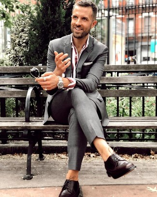 Cómo combinar: reloj plateado, zapatos derby de cuero en marrón oscuro, camisa de vestir de rayas verticales burdeos, traje en gris oscuro