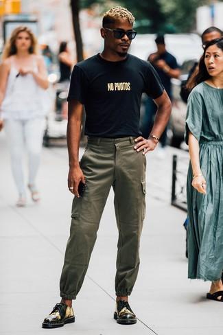 Outfits hombres: Considera ponerse una camiseta con cuello circular estampada negra y un pantalón cargo verde oliva para un look agradable de fin de semana. Dale onda a tu ropa con zapatos derby de cuero estampados negros.