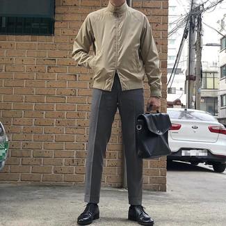 Cómo combinar: portafolio de cuero negro, zapatos derby de cuero negros, pantalón de vestir gris, cazadora harrington en beige