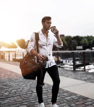 Cómo combinar: bolsa de viaje de cuero en marrón oscuro, zapatos derby de cuero blancos, vaqueros pitillo desgastados negros, camisa de manga larga estampada en blanco y negro