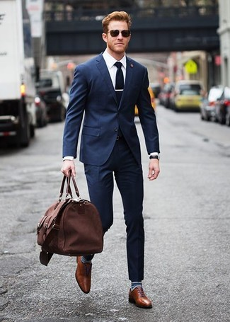 Cómo combinar: bolsa de viaje de lona marrón, zapatos oxford de cuero marrónes, camisa de vestir blanca, traje azul marino
