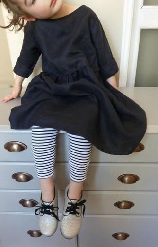 Cómo combinar: zapatos oxford dorados, leggings de rayas horizontales en blanco y negro, vestido de algodón negro