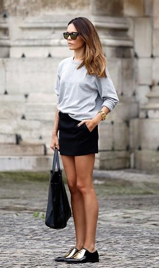 Cómo combinar: bolsa tote de cuero negra, zapatos oxford de cuero en negro y dorado, minifalda negra, camiseta de manga larga gris