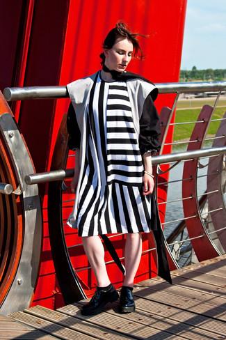 Cómo combinar: bufanda de seda negra, zapatos oxford de cuero gruesos negros, vestido recto de rayas verticales en blanco y negro, gabardina negra