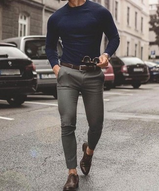 Cómo combinar: correa de cuero en marrón oscuro, zapatos oxford de cuero en marrón oscuro, pantalón chino gris, jersey con cuello circular azul marino